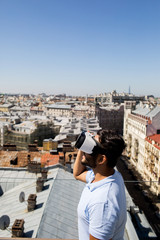 Young modern man in vr headset looking at sun on clear blue sky with cityscape on background