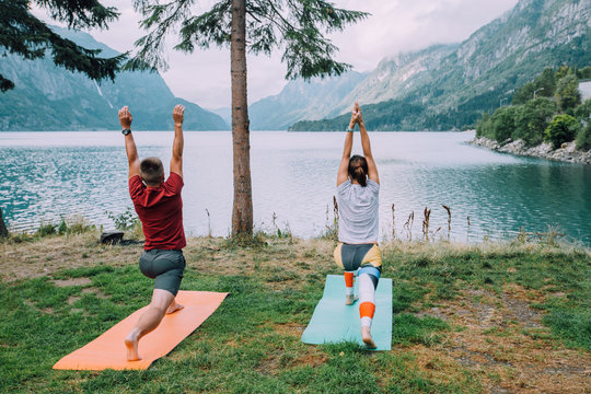 Fitness, sport, friendship and lifestyle concept - sportive couple making yoga exercises on mats in cloudy morning outdoors near beautiful lake in camping, unusually nature, Norway.
