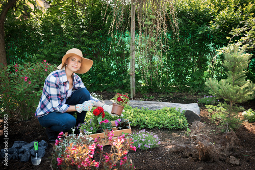 Beautiful Female Gardener Looking At Camera Holding Flowers Ready To Be Planted In Her Garden