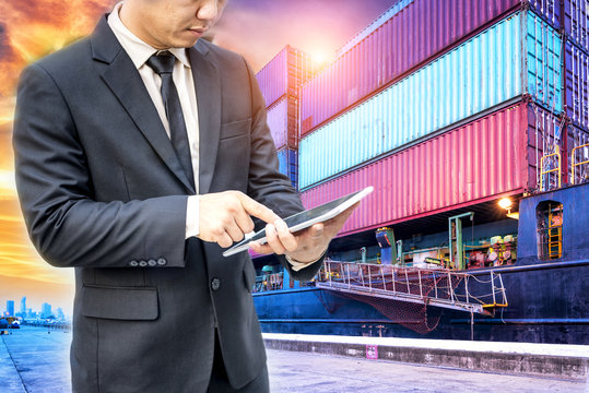Businessman using digital tablet checking scheduled ship standing in the container cargo ship