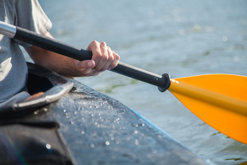 A man's hand holds an oar. Kayak in the sea. Close-up photo.