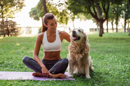 Exercising with her best friend. Young beautiful fit woman in sportswear exercising with the dog while sitting in the park