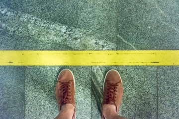 A young man stands on a platform at the warning yellow line in the subway