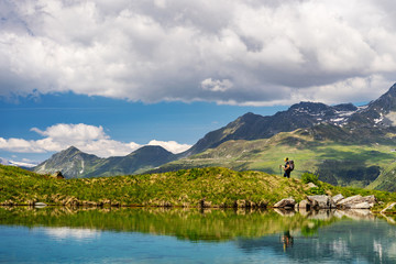 Female traveler with backpack hiking mountain trail next to a mountain lake and admiring views of Swiss Alps in Val de Bagnes area, Switzerland.