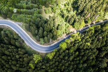 Winding road from high mountain pass, in summer time. Aerial view by drone . Romania