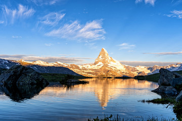 Morning shot of the golden Matterhorn (Monte Cervino, Mont Cervin) pyramid and  blue Stellisee lake. Sunrise view of majestic mountain landscape. Swiss Alps, Zermatt, Switzerland, Europe.