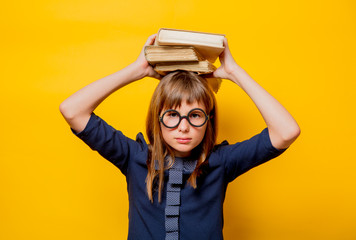 Portrait of a nerd girl in glasses with books on yellow background