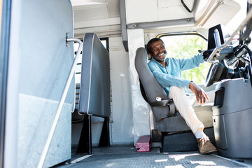 happy mature african american bus driver looking at camera while sitting inside bus