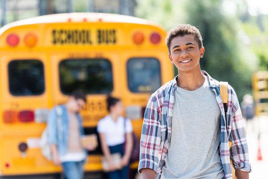 happy teen african american schoolboy looking at camera in front of school bus