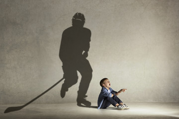 Ice hockey champion. Childhood and dream concept. Conceptual image with boy and shadow of fit athlete on the studio wall