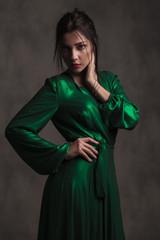 elegant woman in green silk dress looking seductively