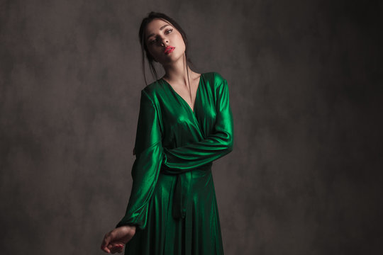 portrait of young woman in green dress leaning to side