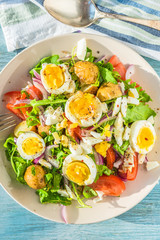 Mediterranean salad with tomatoes, arugula, potatoes and boiled eggs