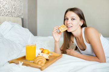 beautiful brunette girl eating a healthy breakfast in bed
