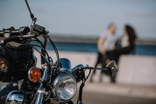 selective focus of vintage classical motorbike with couple on background