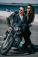 couple of bikers in black leather jackets sitting on classic motorcycle