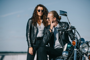 couple of bikers in leather jackets sitting on classical vintage motorcycle