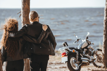 back view of couple hugging and looking at sea, motorbike standing near