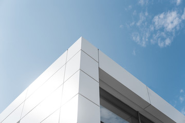 Building with white aluminum facade and aluminum panels against blue sky. Fototapete
