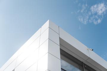 Building with white aluminum facade and aluminum panels against blue sky. Fototapete