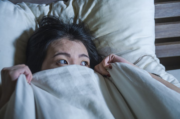young scared and stressed Asian Chinese woman lying in bed suffering nightmare in fear and panic grasping blanket covering her horror face expression