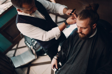 Barbershop with wooden interior. Bearded model man and barber.