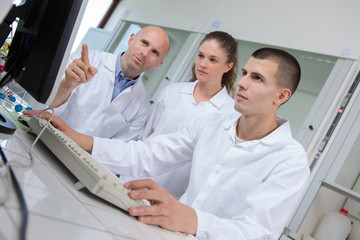 Students and teacher in labcoats loking at computer