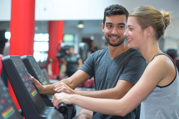 woman doing cardio workout on treadmill with personal trainer