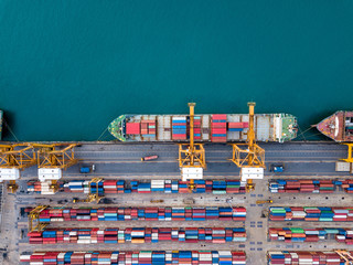Top view of international port with Crane loading containers in import export business logistics.