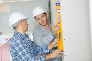 two workers with level indoors