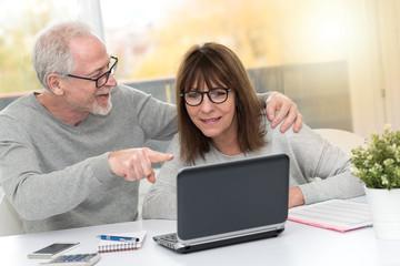 Happy mature couple having a good surprise on laptop, light effect