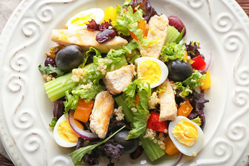 Tasty chicken salad with vegetables and quail eggs on plate, closeup