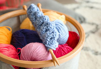Colorful knitting yarn with needles in basket, closeup