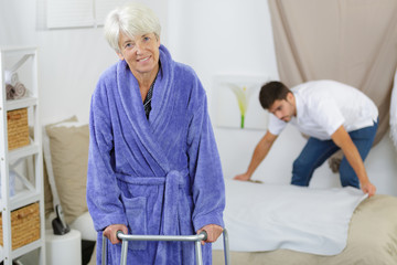 elderly woman ambulates from her bed with a walker