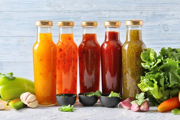 Fotobehang - Bottles with different tasty sauces and vegetables on light table
