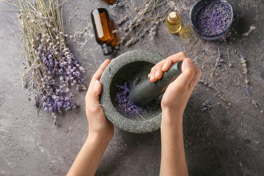 Woman grinding lavender flowers in mortar, top view