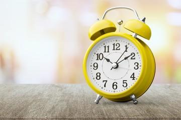 Yellow alarm clock on white backgroundYellow alarm clock on
