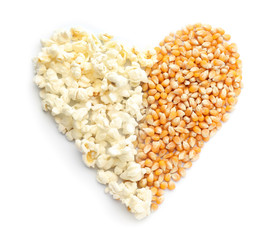 Heart made of delicious popcorn and kernels on white background