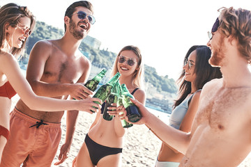 Enjoying carefree time with friends. Cheerful young people spending nice time together while sitting on the beach and drinking beer