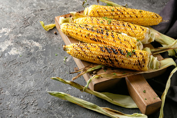 Tasty grilled corn cobs on wooden board