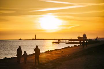 People walking on a pier on sunset