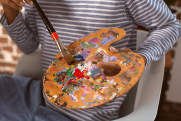 Young African-American artist with palette and brush, closeup
