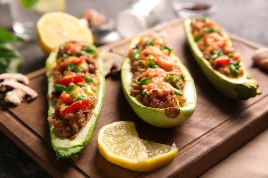 Meat stuffed zucchini boats on board, closeup