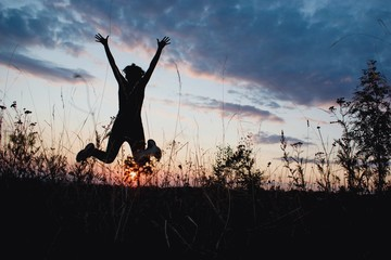 Young woman jumping happily in sunset light. Nature, outdoor, freedom, success, happiness concept
