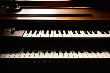 Double keyboard piano detail in natural window light.