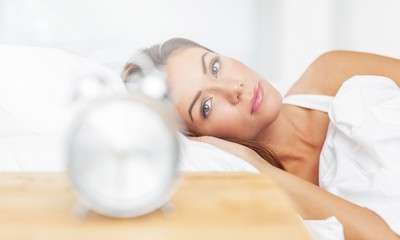 Woman in her bed looks on clock