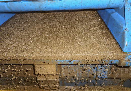 Shale shaker screen close up view with drill cutting flow out from oil base mud