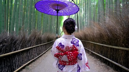 Fototapete - Asian woman wearing japanese traditional kimono at Bamboo Forest in Kyoto, Japan.