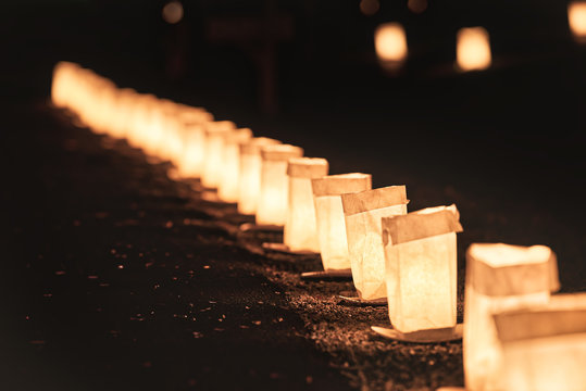 Row, line of Christmas Eve candle lights, lanterns in paper bags at night along road, street, path illuminated by houses in residential neighborhood in Virginia