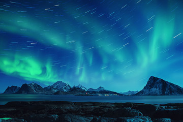Photo sur Toile Aurore polaire Northern Lights, Aurora Borealis shining green in night starry sky with star tracks at winter Lofoten Islands, Norway